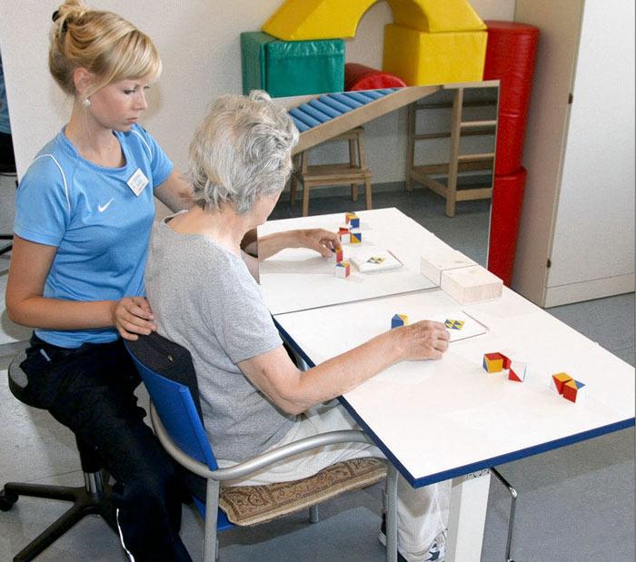 Annika Fricke betreut eine Patientin bei der Spiegeltherapie